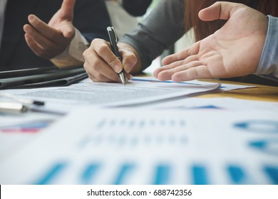 Close up business peple reaching out sheet with contract agreement proposing to sign.Full and accurate details, individual who owns the business sign personally,director of the company, solicitor.