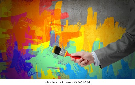 Close up of business person hand holding paint brush