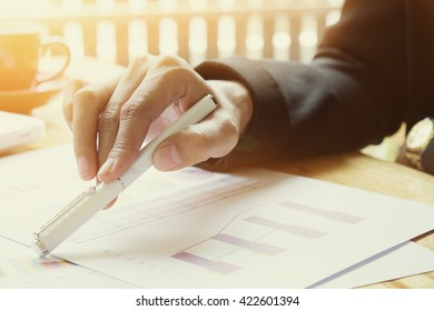Close up of business person hand with pen over paper vintage photo.