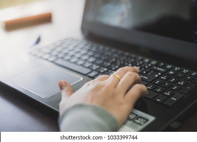 Close up business person's hands using computer on wooden table outside the office in weekend. Woman's hands using laptop computer access internet searching information for work outside work place.