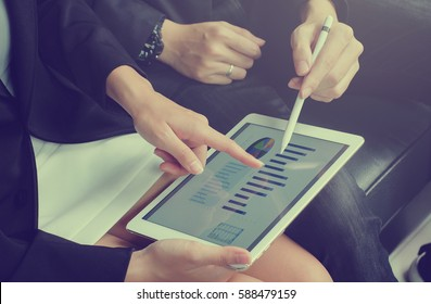 close up business woman hand finger point on screen display tablet for explain detail statistic graph with business man holding stylus pen for teaching.
