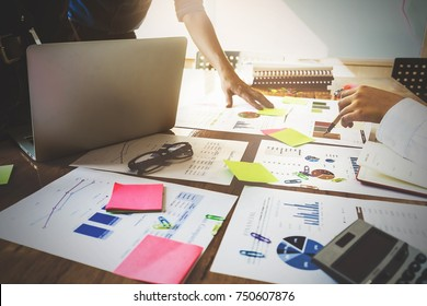 Close up Business woman and partner using calculator and laptop for calaulating finance, tax, accounting, statistics and analytic research, group support and meeting concept