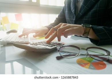 Close up Business woman using calculator and laptop for do math finance on wooden desk in office and business working background, tax, accounting, statistics and analytic research concept - Image