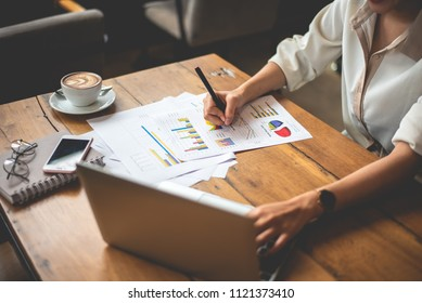 Close up of business woman working with documents and laptop in office. Business and Lifestyles concept. Entrepreneur and Freelance theme.