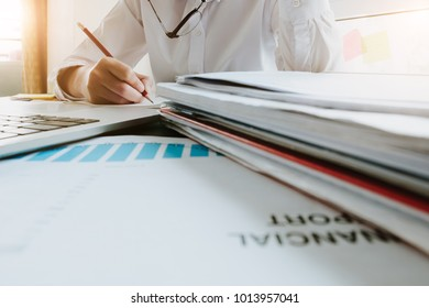 Close up Business women using laptop and note some data on notepad for analysis financial document - Financial concept