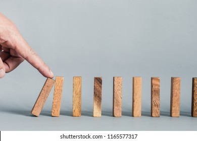 Close up of businessgirl hand Stopping Falling wooden Dominoes effect from continuous toppled or risk, strategy and successful intervention concept for business.