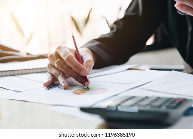 Close up of businessman or accountant hand holding pencil working on calculator to calculate financial data report, accountancy document and laptop computer at office, business concept