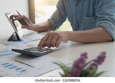 Close up of businessman or accountant hand holding pen working on laptop computer business data, accountancy document and  calculator at office, business concept - Image