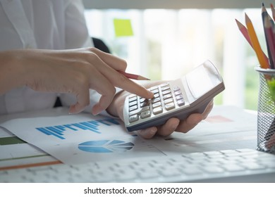Close up of businessman or accountant hand holding pen working on calculator to calculate business data, accountancy document and laptop computer at office, business concept - Image