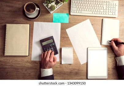 Close up of businessman or accountant hand holding pen working on tablet computer for calculate business data, accountancy document and calculator at office, business concept