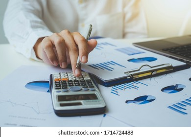 Close up of businessman or accountant hand holding pen using calculator to calculate numbers with business chart data. Accountancy documents and business information on the desk at the office,