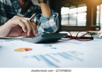 Close up of businessman or accountant working on calculator to calculate business data, and accountancy document. Business financial and accounting concept