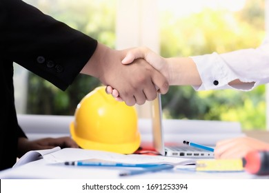 Close up businessman and architect or engineer standing and shaking hand to each other after successful of big project at meeting at office