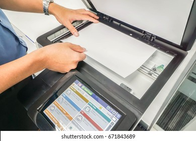 close up businessman in blue shirt hand place paper sheet on printer plate for scanning