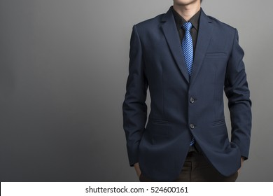 Close up of businessman in blue suit confident on gray background
