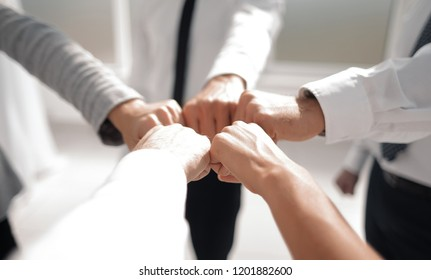 Close up .businessman and businesswoman making a fist bump on building background