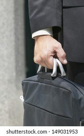 Close up of businessman carrying briefcase