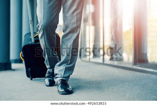 乗客の搭乗橋を歩きながら、スーツケースを持つ実業家の接写。