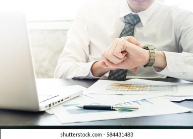 Close up of businessman checking time on his wrist watch.