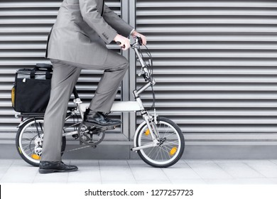 Close up of businessman cycling to work on folding commuter bicycle on pavement