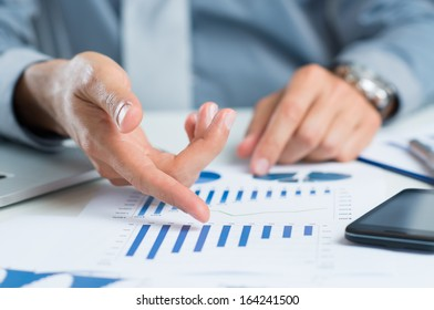 Close Up Of A Businessman At Desk Analyzing Business Graph