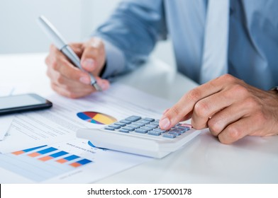 Close Up Of A Businessman With Documents At Desk Doing Calculations