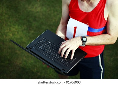 A close up of a businessman dressed in running attire with the number one on his chest, working on his laptop outside.