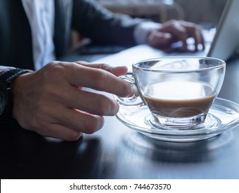 Close up of Businessman drinking coffee and using a laptop on the office desk.