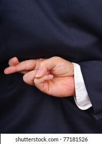 Close up of businessman with fingers crossed behind his back