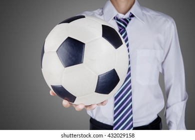 Close up of businessman giving a soccer ball. shot with grey background