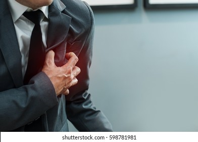 Close up Businessman in grey suit has heart attack. Exhausted, Illness, disease, tired concepts.