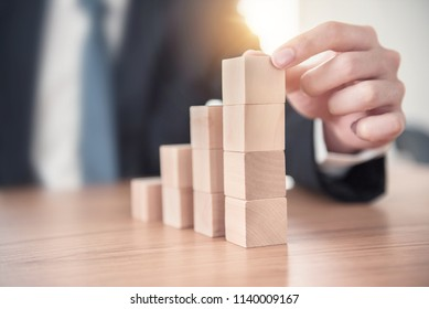 Close up Businessman hand arranging wood cube stacking as step stair. Business concept growth success process.