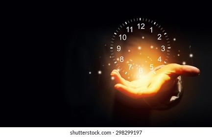 Close up of businessman hand holding clock  icon in palm