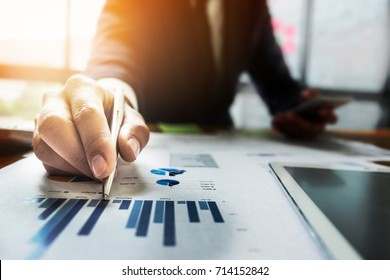 Close up Businessman hand holding pen and pointing at financial paperwork.