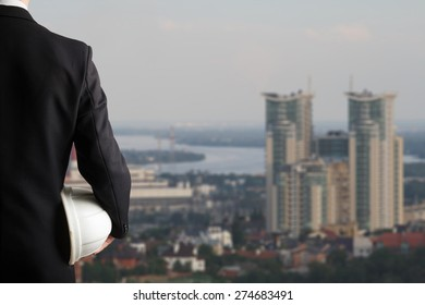 Close up of businessman hand holding white safety helmet for workers security standing in front of blurred urban background.