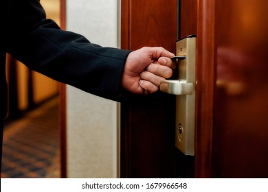 Close up of businessman hand opening the door using key card while entering his room in a luxury hotel. Horizontal shot