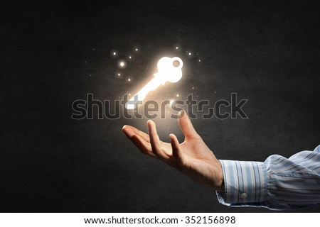 Close up of businessman hand showing key to success