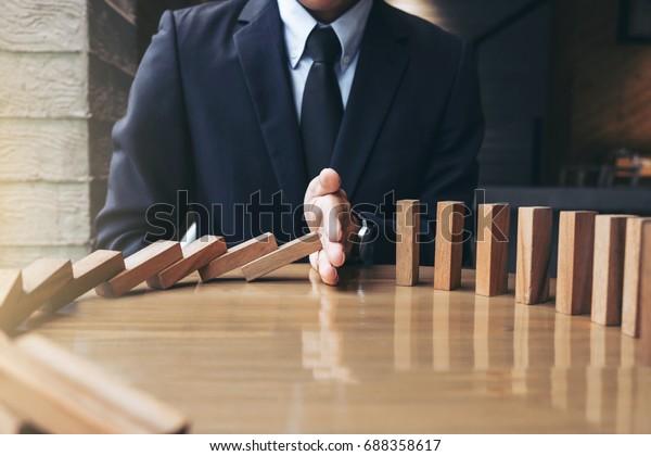 Cierre de la mano de los empresarios Detener la caída de Dominos de madera efecto de continuo derribado o riesgo, estrategia y exitoso concepto de intervención para los negocios.