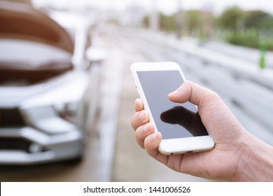 close up businessman hand using a mobile smart phone call a car mechanic ask for help assistance because car broken.
