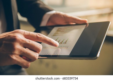 Close up businessman hand using tablet and pointing on summary report at office.Male businessman reviews a summary report on tablet.