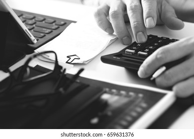 close up of businessman hand working with finances about cost and calculator and laptop with mobile phone on withe desk in modern office ,black and white