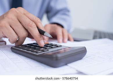 Close up of businessman hand working on accountancy document and calculator, e business concept