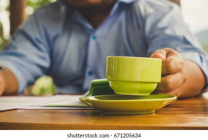 Close up businessman hands hold a cup of coffee on wooden desk