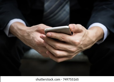 Close up of businessman hands holding smartphone in blurred background.
