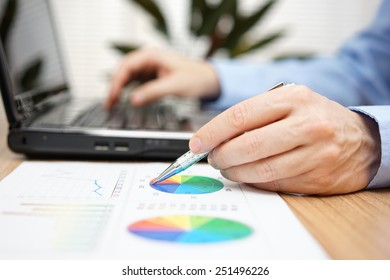 Close up of businessman hands reviewing business report and typing on laptop computer