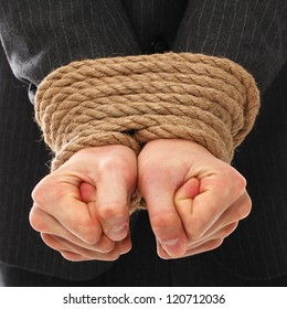 Close up of businessman hands tied with rope together
