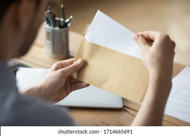 Close up businessman holding envelope with blank paper sheet, focused man looking at letter, received news, notification or invitation, working with correspondence, sitting at work desk - Shutterstock ID 1714665691