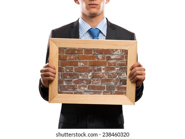 Close up of businessman holding frame with brick texture
