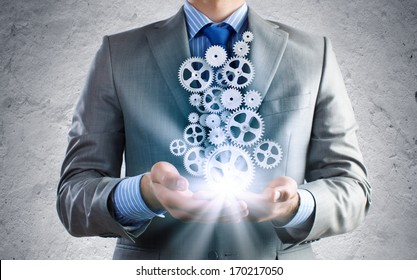Close up of businessman holding gears in palms