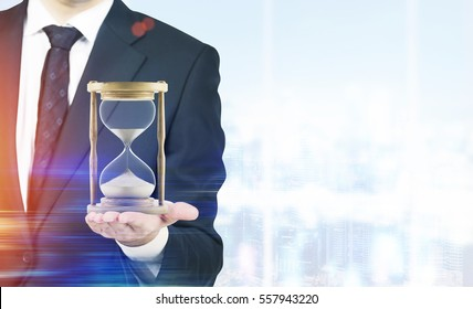Close up of a businessman holding hourglass. Office. Cityscape. Concept of time management. Mock up. Toned image. Double exposure